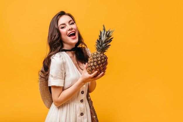 Młoda dama z nagim makijażem trzyma ananasa. kobieta w białej sukni śmieje się na pomarańczowym tle.