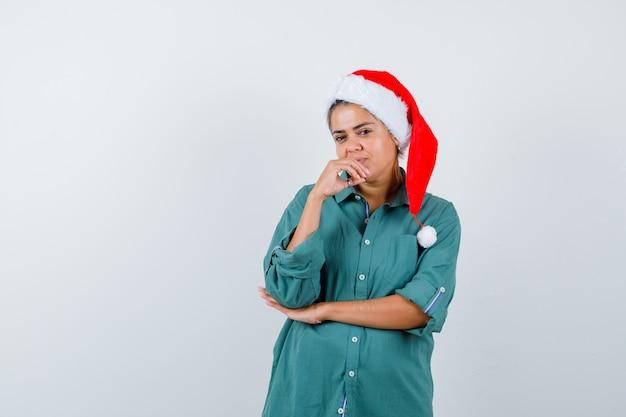 Młoda dama z ręką na brodzie w świątecznym kapeluszu, koszuli i wyglądającym pewnie, widok z przodu.