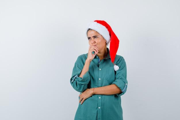 Młoda dama z ręką na ustach w świątecznym kapeluszu, koszuli i patrząc zamyślona. przedni widok.
