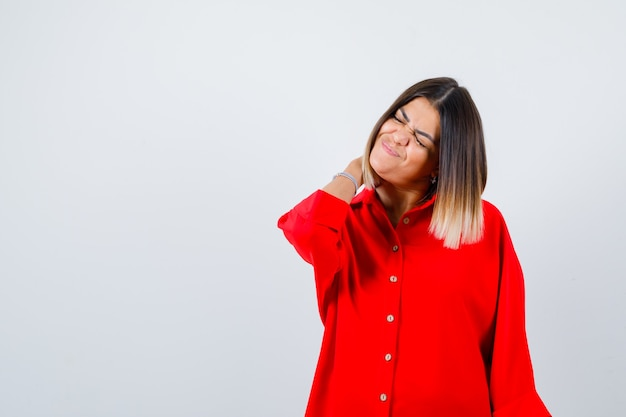 Młoda dama z ręką za szyją w czerwonej koszuli oversize i wygląda na bolesną. przedni widok.