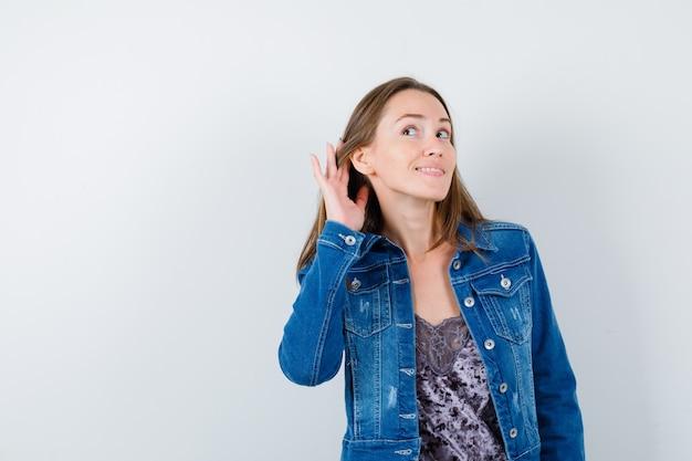 Młoda dama z ręką za uchem w bluzce, dżinsowej kurtce i ładny wygląd. przedni widok.