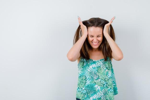 Młoda dama z rękami na głowie i patrząc zirytowana, widok z przodu.