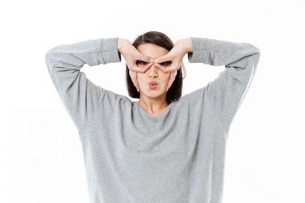 Młoda dama z rękami na twarzy jak okulary