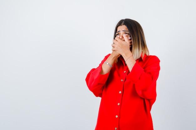 Młoda dama z rękami na ustach w czerwonej koszuli oversize i wygląda na przestraszoną, widok z przodu.