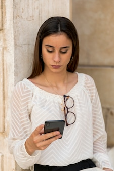 Młoda dama z szkłami na bluzce używać smartphone