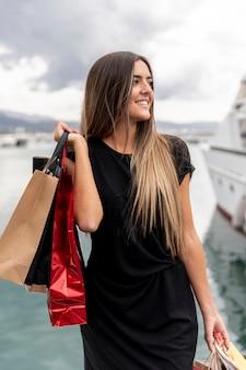 Młoda dama z torby na zakupy patrząc od hotelu