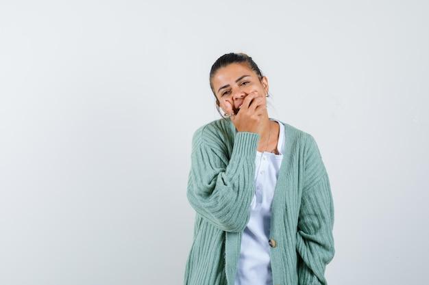 Młoda dama zakrywa usta ręką w koszulce, kurtce i wygląda na szczęśliwą
