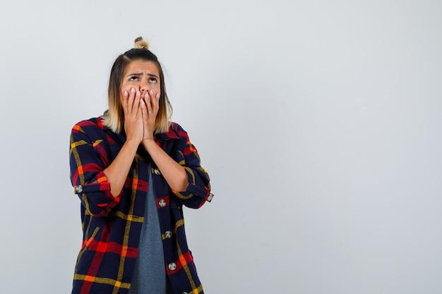 Młoda dama zakrywając usta rękami w dorywczo kraciastej koszuli i patrząc zdenerwowany, widok z przodu.