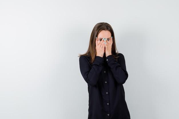 Młoda dama zakrywająca twarz rękami i wyglądająca na zaniepokojoną