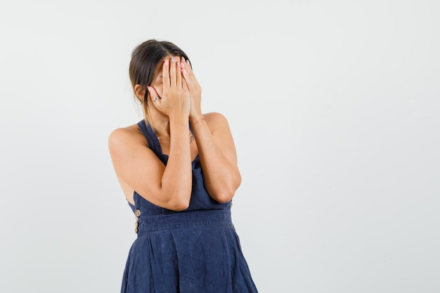 Młoda dama zakrywająca twarz rękami w sukience i wyglądająca na zawstydzoną