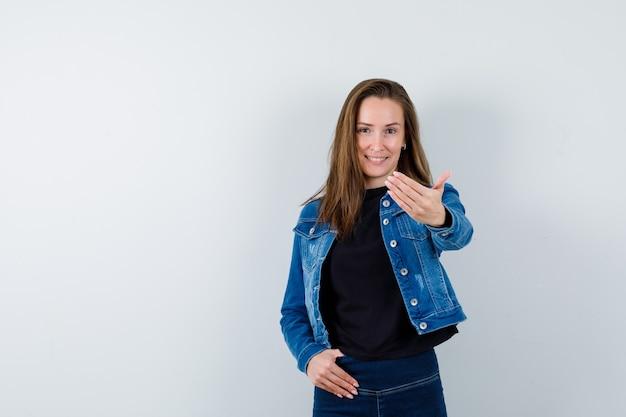 Młoda dama zapraszająca w bluzce, kurtce, dżinsach i wyglądająca pewnie