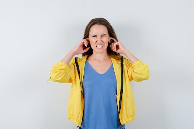 Młoda dama zatyka uszy palcami w koszulce i wygląda na zirytowaną, widok z przodu.