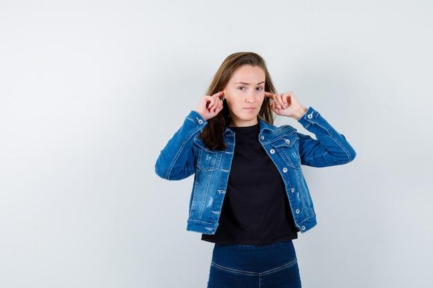 Młoda dama zatykając uszy palcami w bluzce i patrząc pewnie, widok z przodu.
