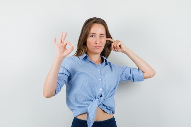 Młoda dama zatykająca ucho, pokazująca znak ok, mrugająca okiem w niebieskiej koszuli