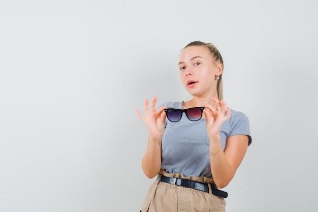 Młoda dama zdejmuje okulary w t-shirt i spodnie i wygląda pewnie