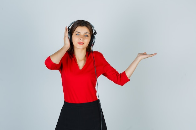 Młoda dama ze słuchawkami, słuchając muzyki, pokazując coś w czerwonej bluzce