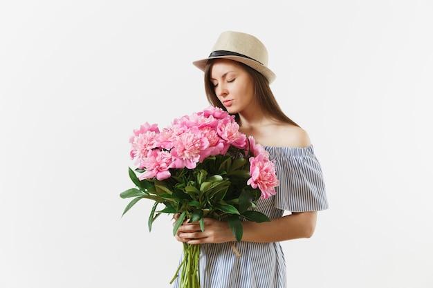 Młoda delikatna kobieta w niebieskiej sukience, trzymając kapelusz, wąchając bukiet kwiatów różowe piwonie na białym tle. dzień świętego walentego, koncepcja wakacje międzynarodowy dzień kobiet. powierzchnia reklamowa.