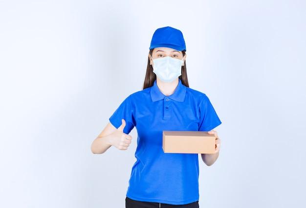Młoda deliverywoman w masce medycznej, trzymając karton i dając kciuk w górę.