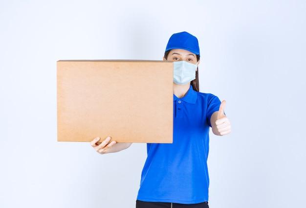 Młoda deliverywoman w masce medycznej, trzymając opakowanie kartonowe i dając kciuk w górę.