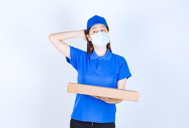 Młoda deliverywoman w masce medycznej, trzymając opakowanie kartonowe.