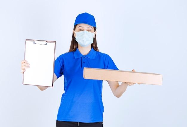Młoda deliverywoman w masce medycznej, trzymając pakiet i schowek.