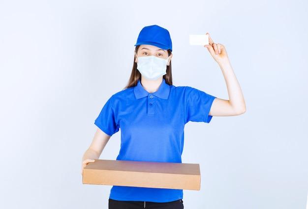 Młoda deliverywoman w masce medycznej, trzymając pakiet i wizytówkę.