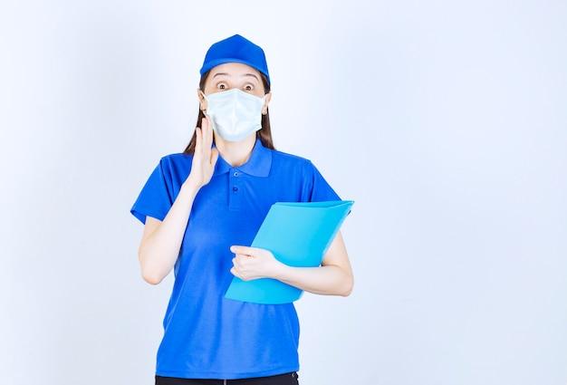 Młoda deliverywoman w masce medycznej, trzymając schowek na białym tle.
