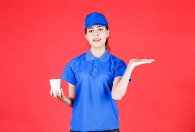 Młoda deliverywoman w niebieskiej czapce trzymając plastikową filiżankę herbaty na czerwono.