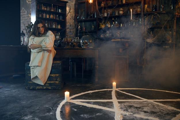 Młoda demoniczna kobieta siedząca w pobliżu magicznego kręgu ze świecami, wyrzucające demony. egzorcyzmy, tajemniczy rytuał paranormalny, mroczna religia, nocny horror, mikstury na półce