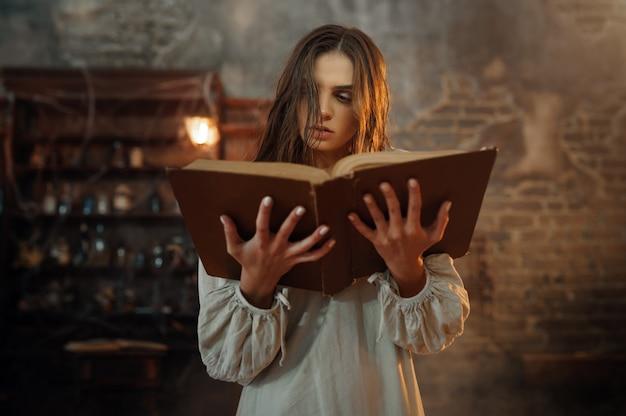 Młoda demoniczna kobieta trzyma księgę zaklęć, wyrzucając demony. egzorcyzmy, tajemniczy rytuał paranormalny, mroczna religia, nocny horror, mikstury na półce