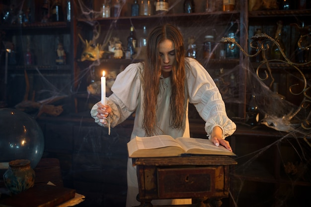 Młoda demoniczna kobieta ze świecą czyta księgę zaklęć, wyrzucając demony. egzorcyzmy, tajemniczy rytuał paranormalny, mroczna religia, nocny horror, mikstury na półce