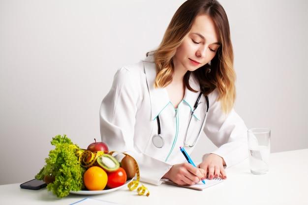 Młoda dietetyk lekarz w pokoju konsultacji przy stole ze świeżymi warzywami i owocami, pracuje nad planem diety