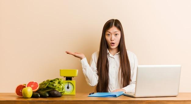 Młoda dietetyka chińska kobieta pracuje z jej laptopem pod wrażeniem trzyma coś na palmie