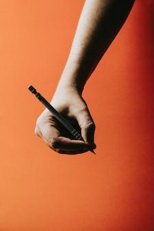 Młoda dłoń chwytająca ołówek automatyczny na pomarańczowym tle z głębokimi cieniami