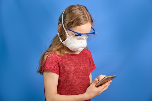 Młoda długowłosa dziewczyna w ochronnej masce medycznej na niebieskiej przestrzeni,