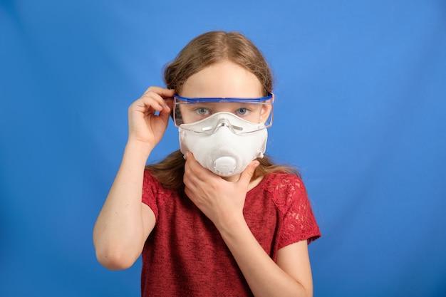 Młoda długowłosa dziewczyna w ochronnej medycznej masce na błękitnej przestrzeni, miejsce dla teksta