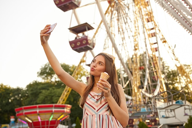 Młoda, długowłosa kobieta pozuje z zaciśniętymi ustami nad parkiem atrakcji, trzymając lody w rożku i robiąc selfie ze swoim smartfonem