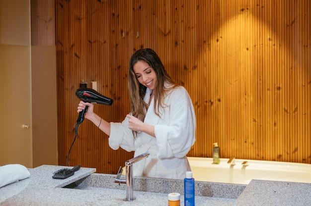 Młoda długowłosa kobieta w białym szlafroku przy użyciu suszarki do włosów po procedurze kąpieli w łazience