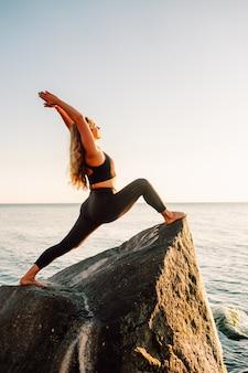 Młoda długowłosa kobieta w pozie wojownika z jogi stojącej na dużym kamieniu w wodzie z rękami do góry. zachód słońca, relaks, medytacja. virabhadrasana.