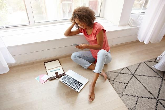 Młoda, dobrze wyglądająca kobieta z brązowymi kręconymi włosami siedzi w pobliżu szerokiego okna i opiera głowę na dłoni, pracuje poza biurem, robi przerwę i pisze sms-y do przyjaciela ze swoim smartfonem