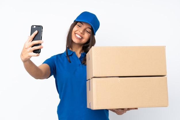 Młoda doręczeniowa brunetki kobieta nad odosobnioną biel ścianą robi selfie