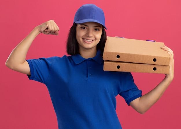 Młoda doręczycielka w niebieskim mundurze i czapce trzyma pudełka po pizzy, unosząc pięść jak zwycięzca, uśmiechając się wesoło, stojąc na różowej ścianie