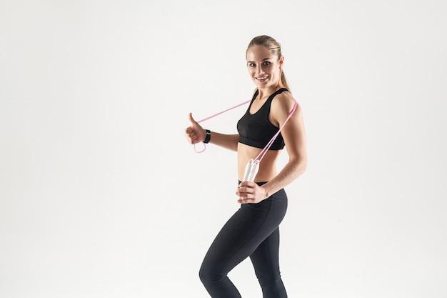 Młoda dorosła blondynka trzyma liny. dziewczyna zajmuje się fitnessem. studio portret dziewczyny dla zdrowego stylu życia.