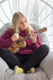 Młoda dorosła blondynka ucząca się grać na ukulele, nauka gry na gitarze online, selektywna ostrość
