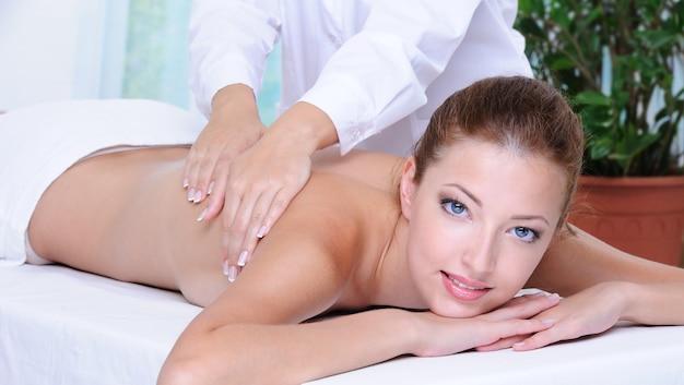 Młoda, dorosła dziewczyna dostaje masaż pleców w gabinecie kosmetycznym