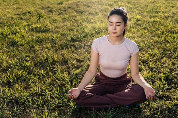 Młoda dorosła dziewczyna o azjatyckim wyglądzie siedzi na trawniku i medytuje.