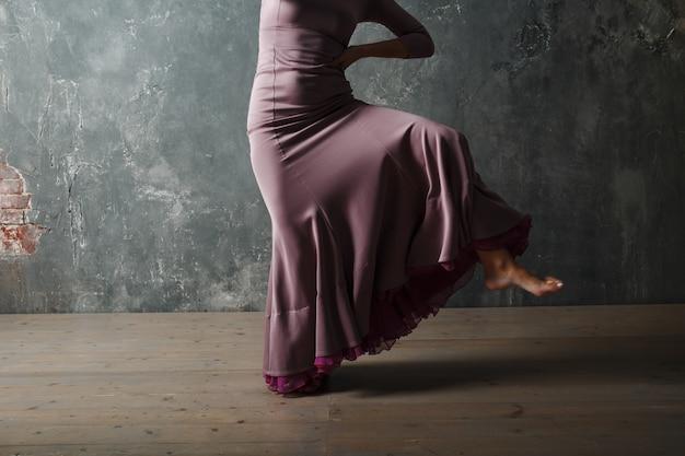 Młoda dorosła hiszpańska kobieta tańczy flamenco na szarym tle studio vintage