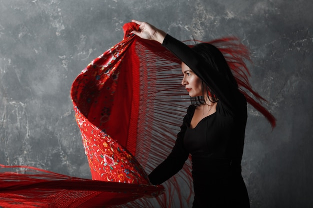 Młoda dorosła hiszpańska kobieta tańczy flamenco na szarym tle vintage