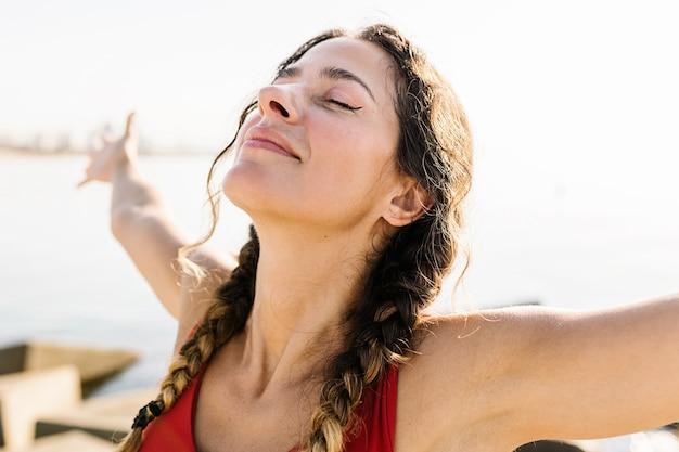 Młoda dorosła kobieta latynoska oddychająca świeżym powietrzem stojąca na plaży latem - portret sportive hiszpanin kobieta relaks nad morzem - koncepcja stylu życia wellness i opieki zdrowotnej