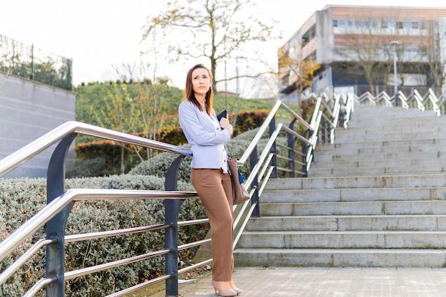 Młoda dorosła kobieta piękna bizneswoman czeka na ulicy dla klienta z laptopem i folderem. pomyślny biznes kobieta koncepcja. kopiuj przestrzeń
